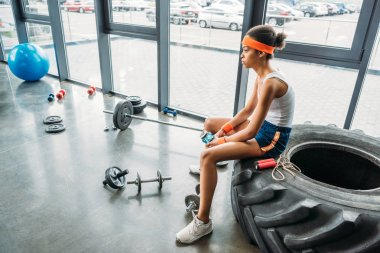 young african american sportswoman in headband and wristbands sitting with bottle of water on training tire at gym