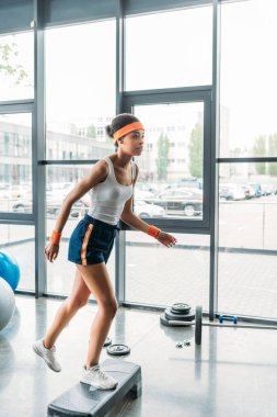 african american sportswoman in headband and wristbands exercising on step platform at gym