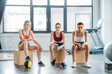 three serious multicultural sportswomen sitting on wooden boxes at gym