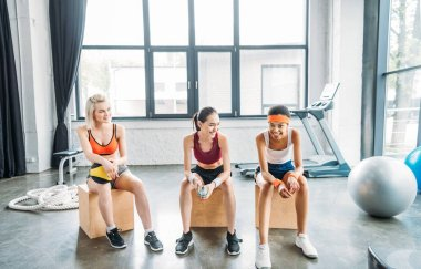 three happy multicultural resting on wooden boxes at gym