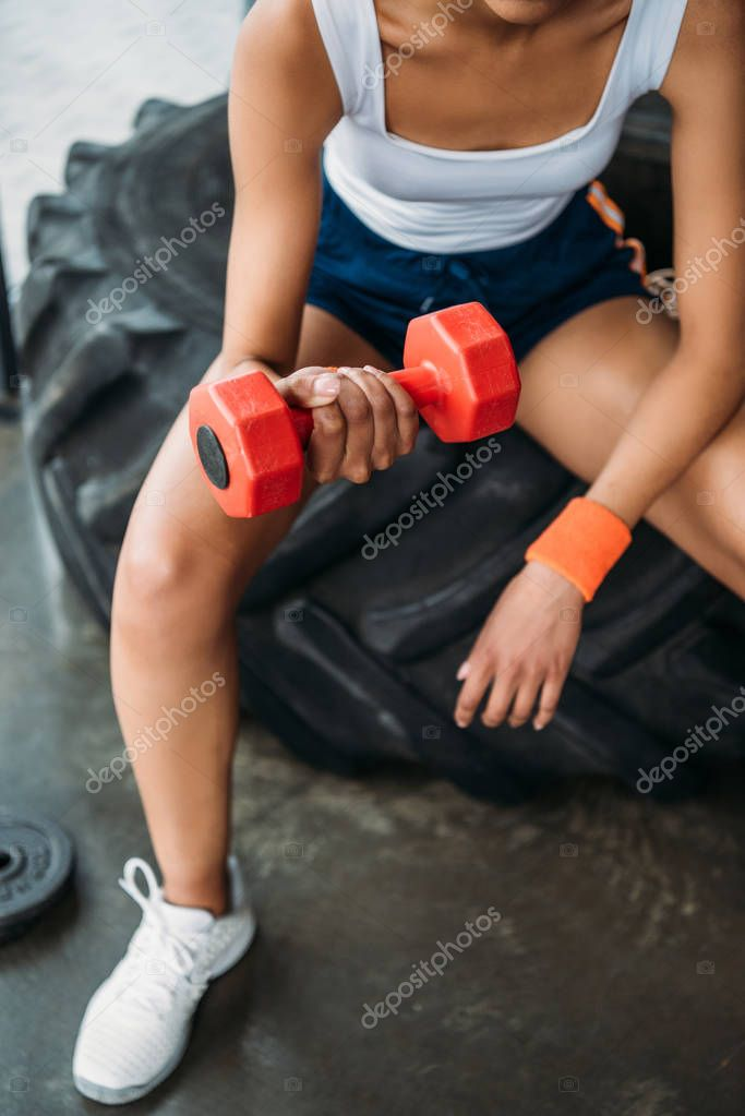 cropped image of female athlete exercising with dumbbell and sitting on training tire at gym