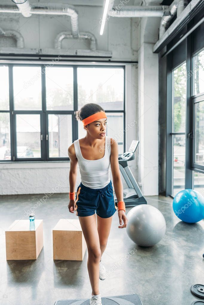young african american sportswoman in headband and wristbands exercising on step platform at gym