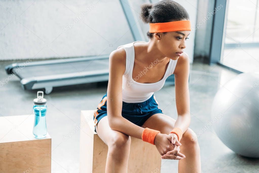 attractive african american sportswoman in headband and headbands resting on wooden box at gym