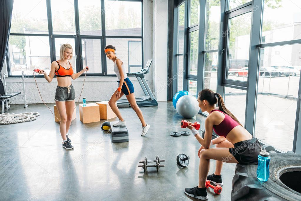three smiling multicultural sportswomen exercising at gym