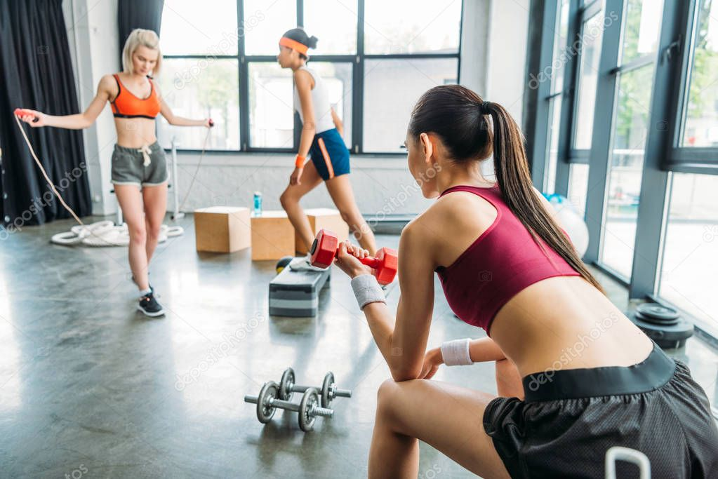 young sportswoman doing exercise with dumbbell while two female athletes training behind at gym