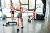 a sportoló csinálás ugrókötél, afro-amerikai női sportoló lépés platform és ázsiai sportoló csinál gyakorlás-val tornaterem súlyzó edzés edzés hátsó nézet