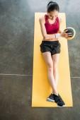 Fotografie erhöhten Blick auf asiatischen Sportlerin mit Ball auf Fitness Matte zu Fitness-Studio trainieren