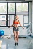 Fotografie attraktive junge Sportlerin auf Springseil im Fitness-Studio trainieren