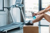 Photo cropped shot of sportswoman sitting on wooden box with bottle of water in front of treadmill at gym