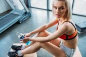 boční pohled na atraktivní sportovkyně s položenou na dřevěných beden po zacvičit v tělocvičně sportovní láhev s vodou