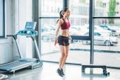Fotografie Seitenansicht des jungen asiatischen Sportlerin mit Springseil im Fitness-Studio trainieren