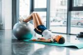 Fotografie boční pohled africká americká sportovkyně na rohož cvičení s fitness míč v tělocvičně