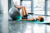 Photo side view of african american sportswoman on mat exercising with fitness ball at gym