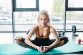 Fotografie Junge sportliche Frau stretching auf Fitness-Matte in Turnhalle