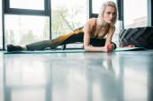 Fotografie mladá žena sportovní strečink na fitness mat v tělocvičně