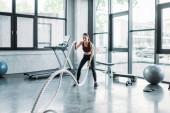 Fotografie asiatische Sportlerin mit Schlacht Seile im Fitness-Studio trainieren