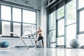 Fotografie Junge Sportlerin mit Schlacht Seile im Fitness-Studio trainieren