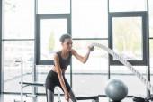 Fotografie lächelnde afroamerikanische Frau mit Schlacht Seile im Fitness-Studio trainieren