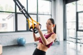 Photo side view of asian female athlete training with resistance bands at gym