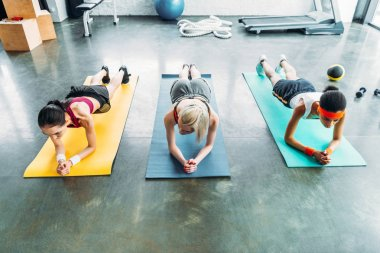 three young multicultural sportswomen doing plank at gym