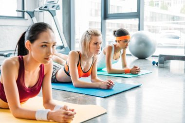 multicultural female athletes exercising on fitness mats at gym