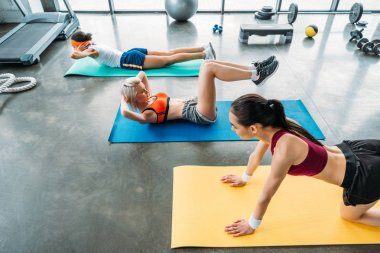 young multiethnic sportswomen exercising on fitness mats at gym