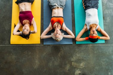 elevated view of multicultural female athletes exercising on fitness mats at gym