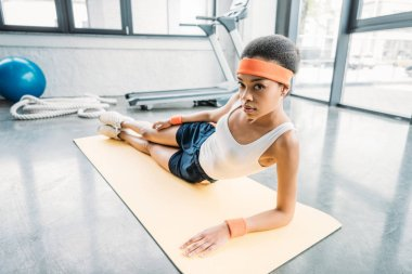 attractive african american female athlete exercising on fitness mat and looking at camera at gym