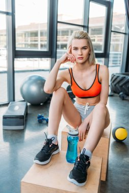 young attractive sportswoman with sportive water bottle resting on wooden boxes after work out at gym