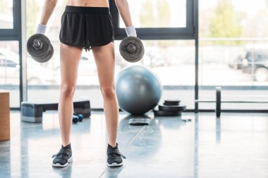cropped shot of sportswoman holding dumbbells in hands at gym