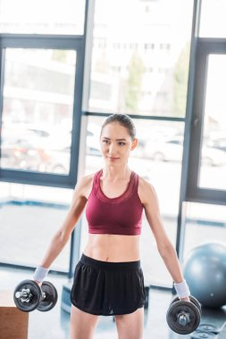 portrait of young asian sportswoman with dumbbells at gym