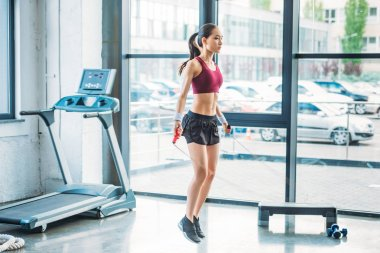 side view of young asian sportswoman exercising with skipping rope at gym