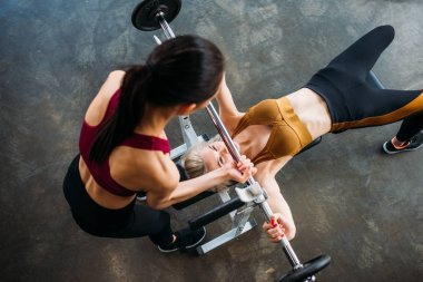 overhead view of female trainer helping young sportswoman weightlifting at gym