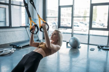 young caucasian sportswoman training with resistance bands at gym