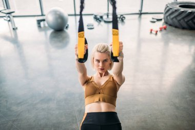 portrait of caucasian sportswoman training with resistance bands at gym