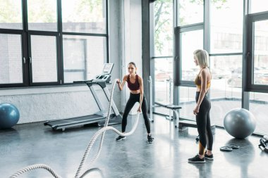 female trainer looking at asian sportswoman working out with battle ropes at gym