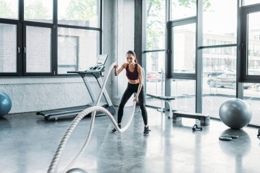 asian sportswoman working out with battle ropes at gym
