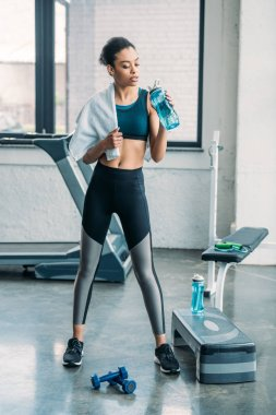 african american sportswoman with sportive water bottle and towel after workout at gym
