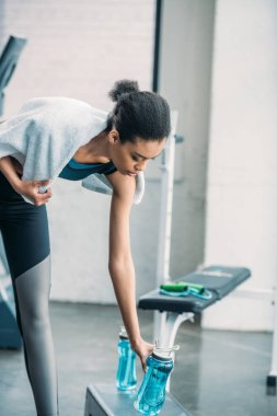 african american sportswoman with towel taking sportive water bottle after workout at gym