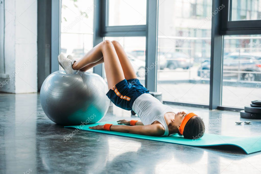 side view of african american sportswoman on mat exercising with fitness ball at gym