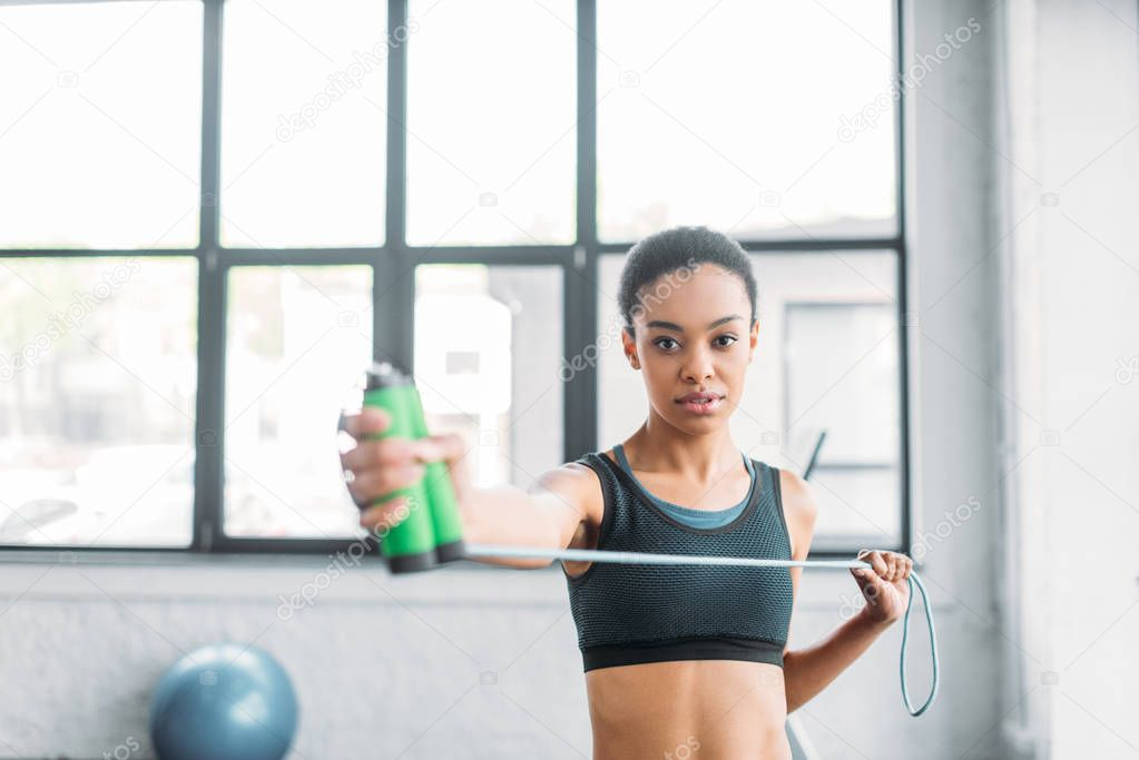portrait of young african american sportswoman with jumping rope at gym