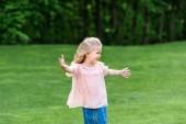 Fotografie roztomilý šťastné malé dítě s otevřenou náručí koukal v parku