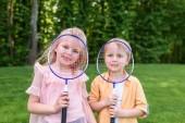 Fotografie roztomilý malý děti drží badmintonové rakety a usmívá se na kameru v parku