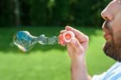 boční pohled vousatý muž foukání mýdlové bubliny v parku
