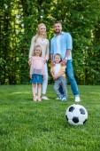 Detailní pohled fotbalový míč na trávu a šťastné rodinné stojící v parku