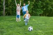 šťastná rodina hraje s fotbalovým míčem v parku