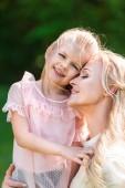 šťastný matka a dcera objímat a usmíval se v parku