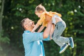 happy father carrying adorable little son in park