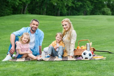 happy family with two children smiling at camera while sitting together on plaid at picnic in park