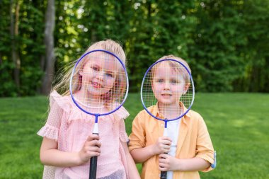 cute little kids holding badminton rackets and smiling at camera in park